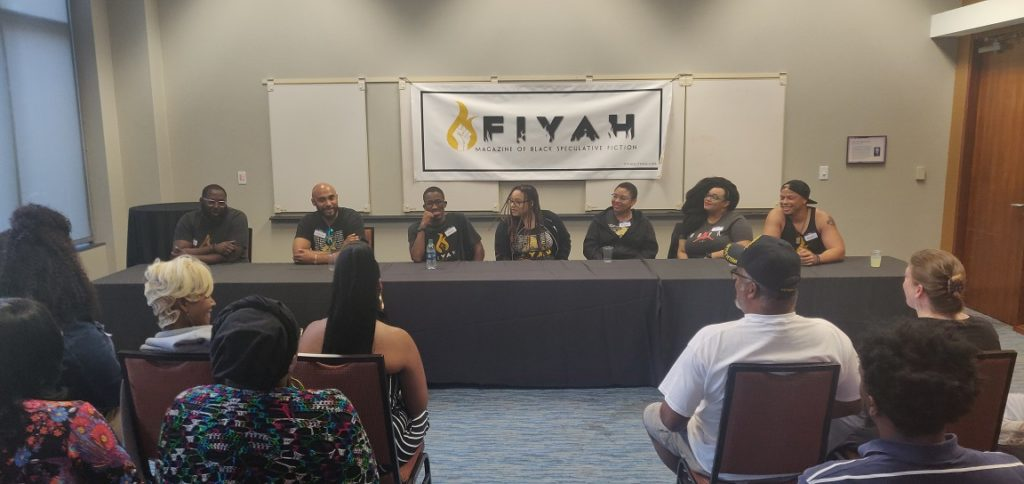 A photo of FIYAH Magazine staff seated before a crowd, leading a panel discussion. There is a banner with their logo on it hanging behind them.
